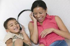 Mère et fils se trouvant sur le sofa partageant des écouteurs Photographie stock libre de droits