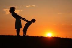 Mère et fils sur la fixation de coucher du soleil à la main Photographie stock libre de droits