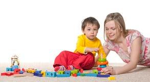 Mère et fils sur le tapis avec des jouets Photos stock