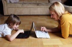 Mère et fils travaillant sur deux petits ordinateurs portatifs Photos stock