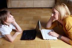 Mère et fils travaillant sur deux petits ordinateurs portatifs Photographie stock
