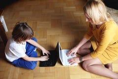 Mère et fils travaillant sur deux petits ordinateurs portatifs Image stock