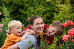 Mère et gosses riants dans le jardin Images libres de droits