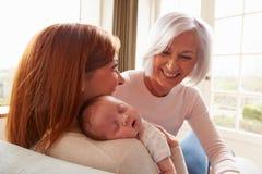 Mère et grand-mère avec la fille nouveau-née de sommeil de bébé Images libres de droits