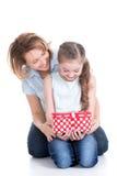 Mère et jeune fille regardant dans la boîte avec le cadeau Image libre de droits