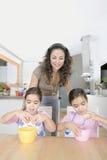 Mère et jumeaux battant des oeufs dans la cuisine Photos libres de droits