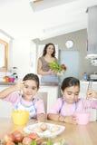 Mère et jumeaux battant des oeufs dans la cuisine Image stock