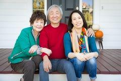 Mère et père adultes supérieurs chinois heureux avec le jeune adulte DA images libres de droits