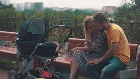 Mère et père avec la voiture d'enfant sur le banc Selfie de prise sur le smartphone famille banque de vidéos