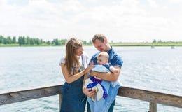 Mère et père avec le fils de bébé se tenant sur le pilier à côté de la rivière photographie stock