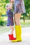 Mère et petite fille adorable d'enfant dans des bottes en caoutchouc ayant l'amusement Image libre de droits