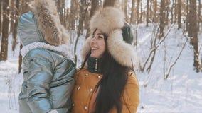 Mère et petite fille appréciant Sunny Weather froid en parc d'hiver banque de vidéos
