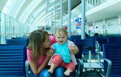 Mère et petite fille attendant dans l'aéroport Photographie stock libre de droits