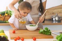 Mère et petite fille faisant cuire le petit déjeuner savoureux de la salade fraîche Tomates de découpage en tranches et de mélang Image libre de droits
