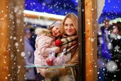 Mère et petite fille mangeant la pomme crystalized sur Noël Images stock