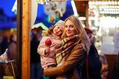 Mère et petite fille mangeant la pomme crystalized sur Noël Images libres de droits