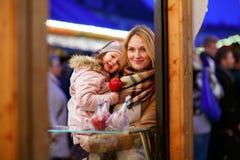 Mère et petite fille mangeant la pomme crystalized sur Noël Image libre de droits