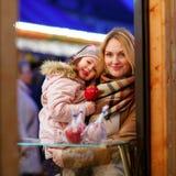 Mère et petite fille mangeant la pomme crystalized sur Noël Photo stock