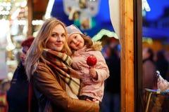 Mère et petite fille mangeant la pomme crystalized sur Noël Photos stock
