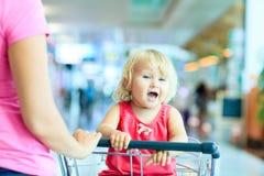 Mère et petite fille mignonne sur le chariot de bagage dedans Images libres de droits