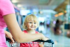 Mère et petite fille mignonne sur le chariot de bagage dedans Photographie stock libre de droits