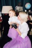 Mère et petite fille posant dans l'intérieur de nouvelle année Image stock
