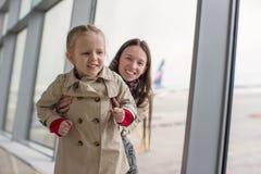 Mère et petite fille près de la fenêtre sur le terminal d'aéroport Photo stock