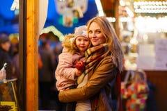 Mère et petite fille sur le marché de Noël Images stock