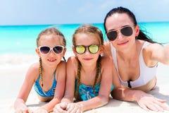 Mère et petites filles prenant le selfie à la plage se trouvant sur le sable blanc Selportrait heureux de prise de famille détend image libre de droits