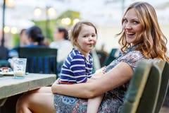 Mère et peu café potable de fille adorable d'enfant dans c extérieur photos libres de droits