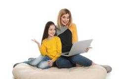 Mère et sa fille employant la causerie visuelle sur l'ordinateur portable photos stock
