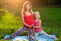 Mère et sa fille faisant dehors le yoga photographie stock