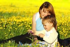 Mère et sa pièce d'enfant sur le pré Photographie stock libre de droits