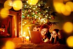 Mère et ses filles lisant un livre Images stock