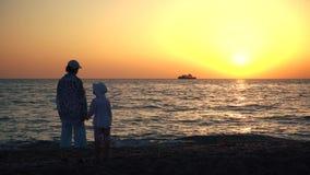 Mère et silhouettes et coucher du soleil d'enfant au-dessus de la mer banque de vidéos