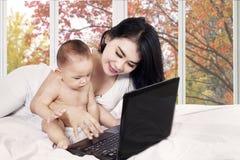 Mère et son bébé à l'aide de l'ordinateur portable Images stock