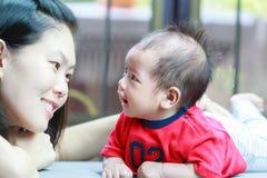 Mère et son bébé regardant entre eux Image stock