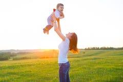 Mère et son enfant jouant au printemps le champ Image stock
