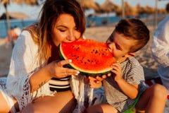 Mère et son fils mangeant la pastèque Photographie stock
