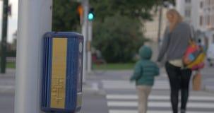 Mère et traverser la route sur le feu vert banque de vidéos