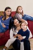 Mère et trois enfants s'asseyant à la maison ensemble photo stock
