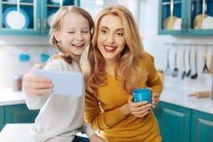 Mère exubérante et fille prenant des selfies Images stock