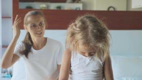 Mère fâchée grondant sa fille tout en se reposant sur le lit dans la chambre à coucher à la maison banque de vidéos