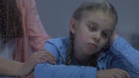 Mère frottant doucement la petite fille bouleversée s'asseyant près de la fenêtre pluvieuse, appui banque de vidéos