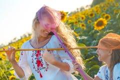 Mère gaie et sa fille jouant dans un domaine avec l'insecte Photographie stock