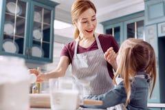 Mère gaie et sa petite liaison de fille tout en faisant cuire au four Image stock