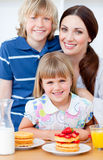 Mère gaie et ses enfants mangeant des gaufres Photo stock