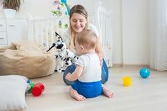 Mère gaie faisant le spectacle de marionnettes avec son bébé garçon adorable Image stock