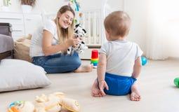 Mère gaie jouant dans le spectacle de marionnettes avec son bébé garçon Photos libres de droits