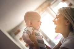 Mère gaie tenant sa haute disponible de petit bébé garçon photo stock